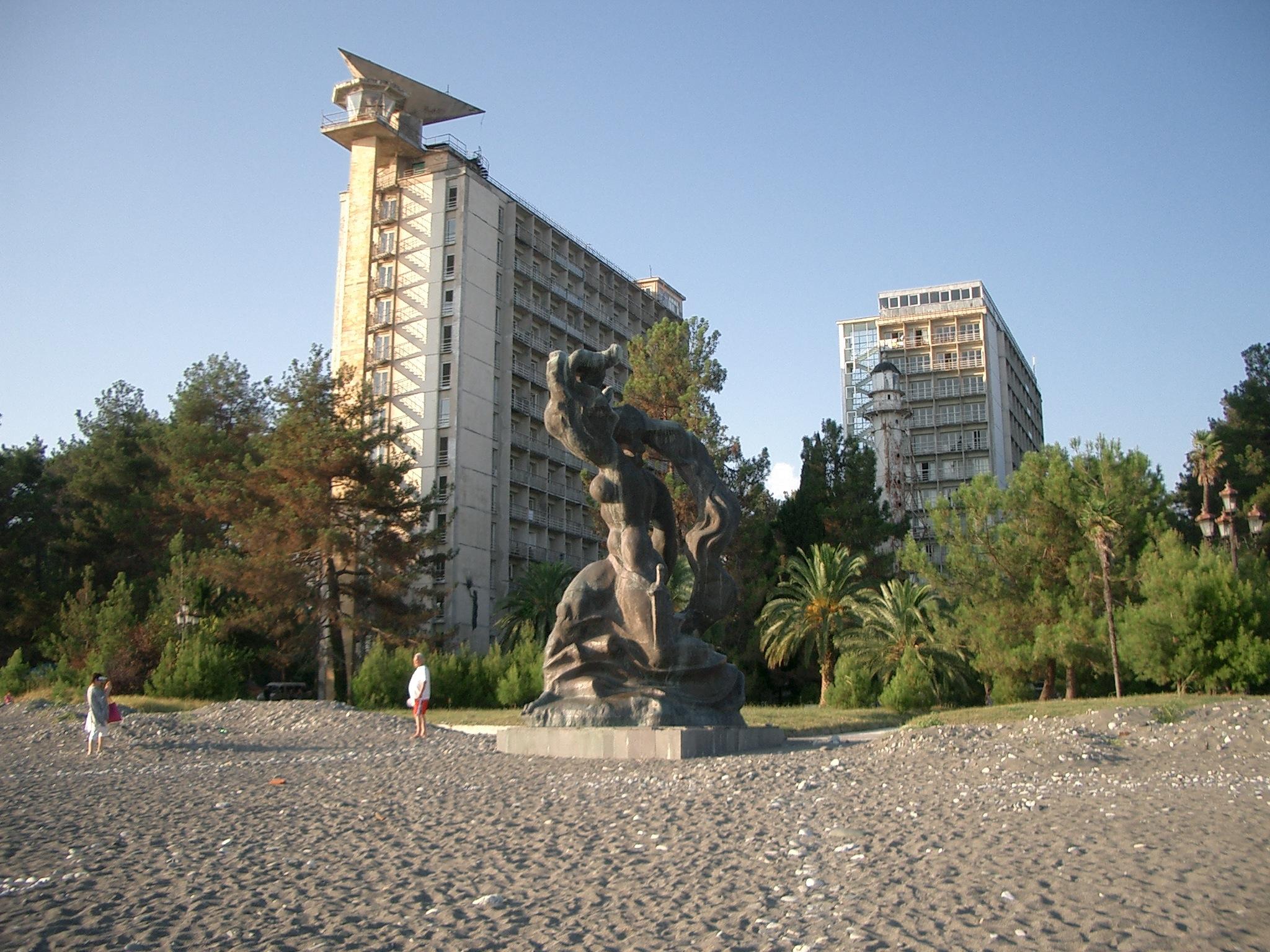 Neuvostolaista hotelliarkkitehtuuria ja pari turistia Pitsundan mäntyisellä niemellä. Huomaa pienehkö isänmaallis-sosialistinen naishahmo etualalla.