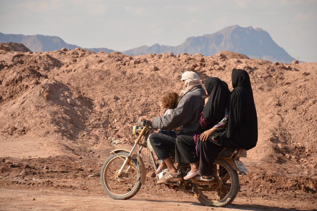 Kolme afgaanipakolaista istuvat pyörän kyydissä.