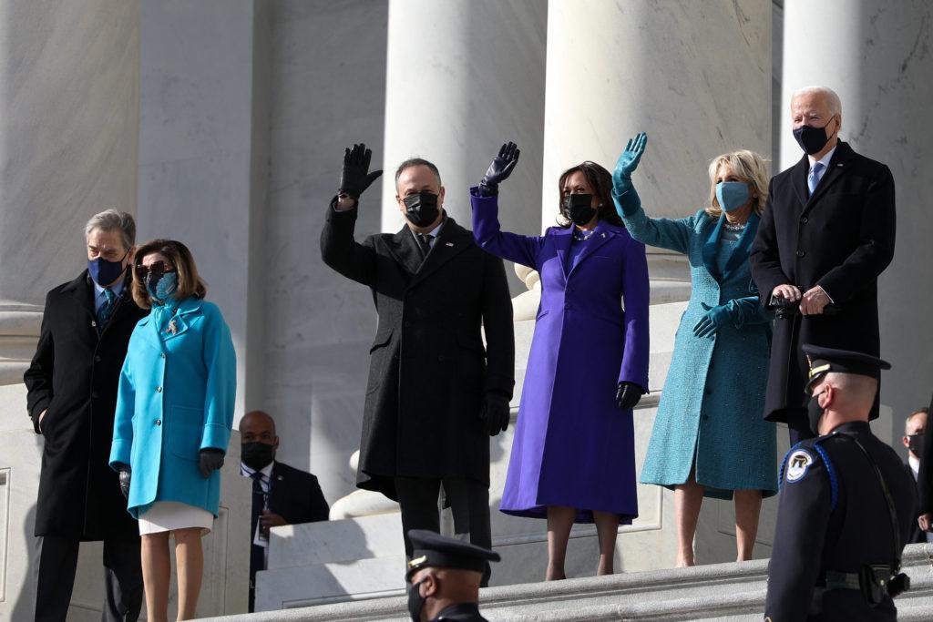 Presidentti Joe Biden ja varapresidentti Kamala Harris seisovat puolisoineen Capitol-kukkalan portailla virkaanastujaispäivänä vilkuttamassa.
