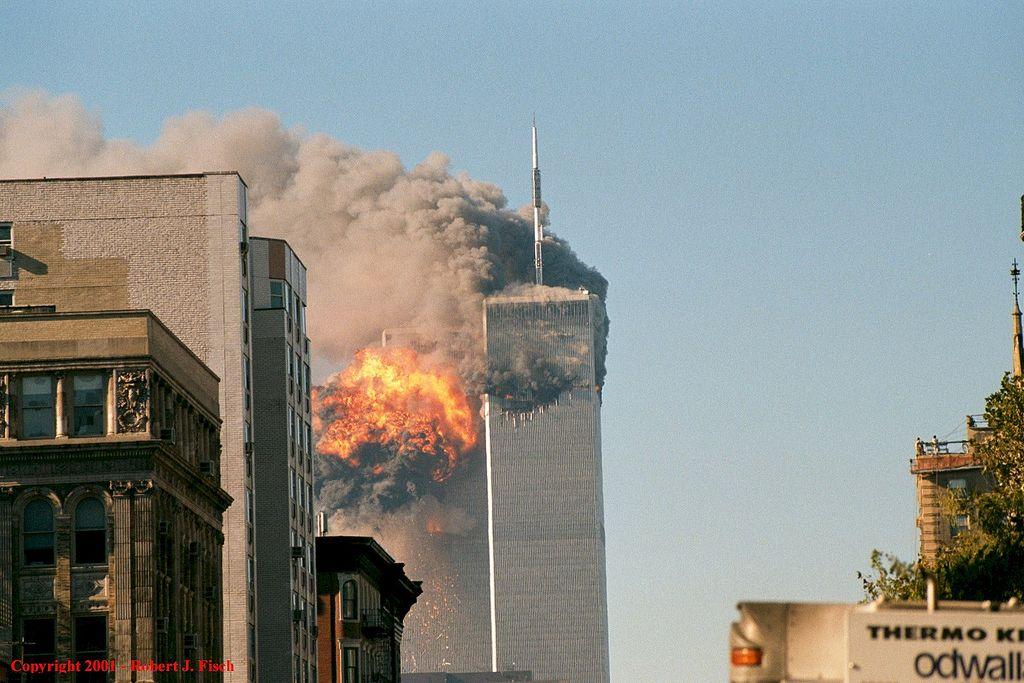 Kuvassa on New Yorkin WTC kaksoistornit, jotka molemmat savuavat ja toisessa on tapahtunut räjähdys.